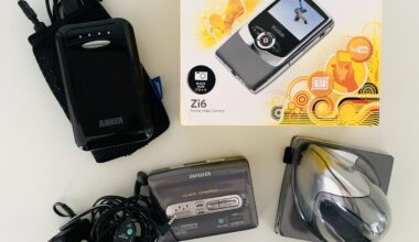Photo of an Aiwa walkman, a Kodak vlogging camera in its original box, an ergonomic mouse, and a power bank. The items are lying on a white table and photographed from above.