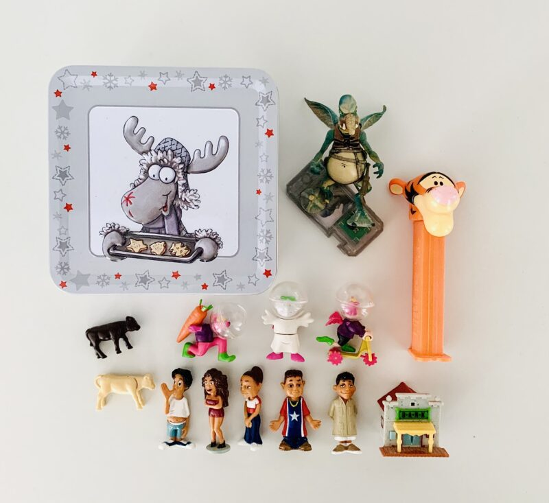 Image shows photo of decluttered, tiny toys photographed on a white table from above. Items include Kinder Egg surprises, a PEZ dispenser with Tigger the Tiger, a Star Wars figure, and little plastic animals. On the upper left is a square, light grey tin with a moose on it dressed in a Christmas outfit and holding a tray of cookies.