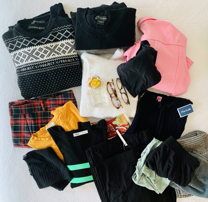 Photo of clothing items sorted out from the closet. The clothes are neatly folded on a bed with a white bedspread, and include jumpers, trousers, underwear, two pairs of glasses, sweaters, t-shirts, and even a bottle of Marc Jacobs perfume.