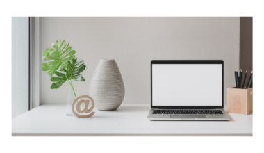 Picture of a very tidy, umcluttered white desk with a laptop open to an empty screen. To the right of the laptop is a pen holder containing pencils. To the left is an empty off-white pottery vase, next to which is a solitary green plant leaf in a slim glass vase. In front of the vases is a small wooden carving of the @ sign. The workspace appears very organized and decluttered.