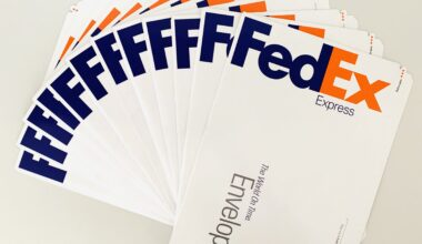Photograph of 12 FedEx mailing envelopes spread out in a fan on a white table.