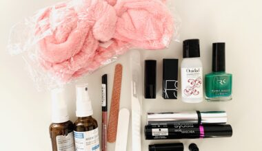 Photograph of assorted makeup and cosmetic items that were decluttered from the bathroom. Items include a big pink microfiber headband, small spray bottles, nail varnish, mascara, a nail file and lip pencil, and lipsticks. The items are neatly arranged on a white table and photographed from above.