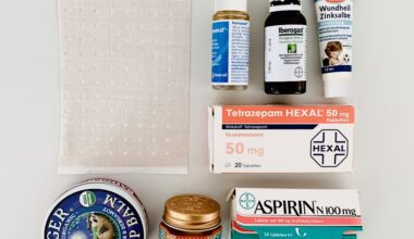 Photo of a tidy arrangement of items which were decluttered from the bathroom medicine chest. The apothecary items are arranged neatly on a white table and photographed from above. We can see a packet of expired aspirin, some zinc salve, tiger balm, a plaster and assorted drops and gels.
