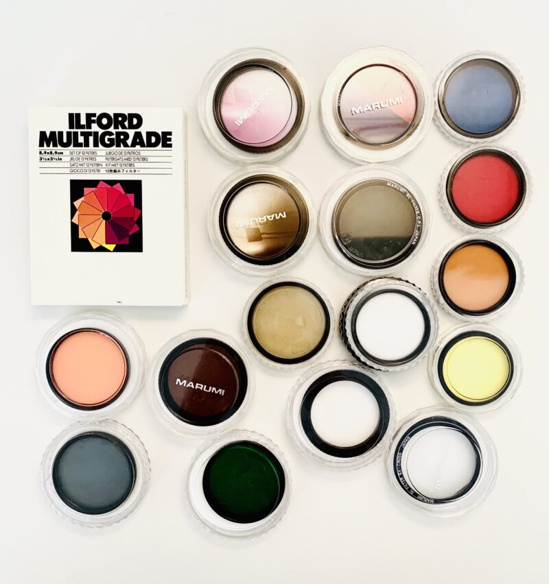 Photo of a very tidy, clean selection of new photographic filters for camera lenses in a variety of bright colours. The filters are round, 52mm to 58mm large, and in their plexiglass cases. There are about 16 such photographic filters laid out on a white table, and in the upper left is a box of Ilford Multigrade gelatine filters for the darkroom as well.