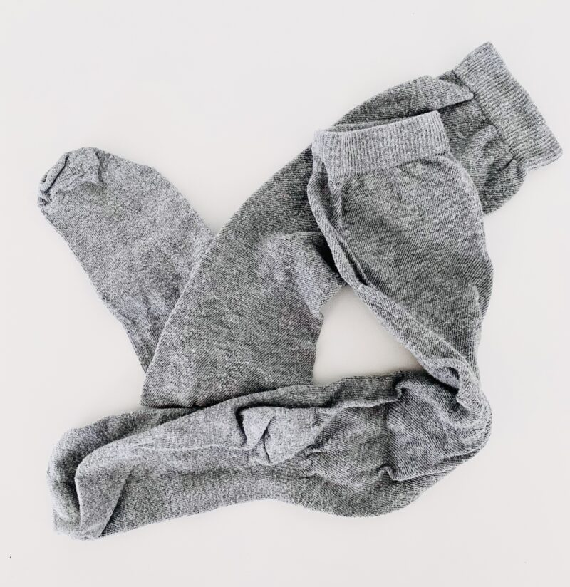 Photo of a pair of light grey socks against a white background.