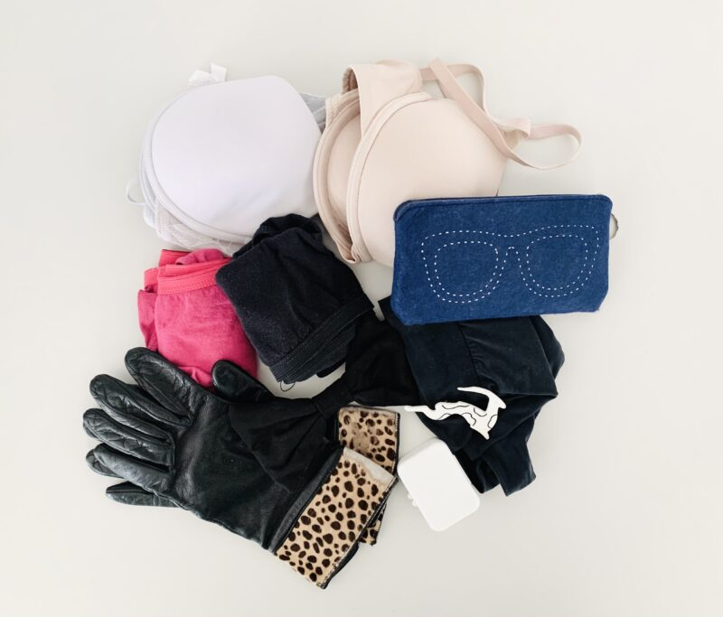 Photograph of underwear, gloves, bras and an eyeglass pouch that were decluttered from the closet during a 30 day tidyup challenge. The items are photographed from above against a white background.
