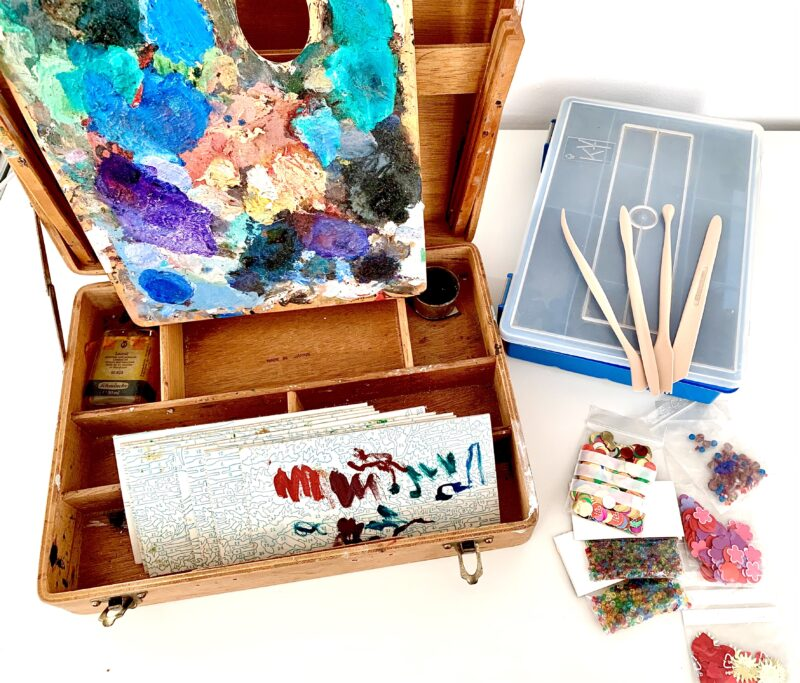 Photo of an old wooden oil paint kit from the 1960s, rather beaten up. Propped against it is the artist's palette with layers and layers of dried up, bright oil paints. Inside the kid is an empty terpentine bottle and some cut up paint by numbers boards to test the paints on. Next to the kit are some craft supplies such as beads, paper cut-outs, clay tools, and a plastic box to organise small bits in. The items are placed on a table table in front of a white wall.