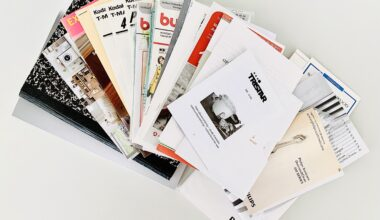 Photo of a decluttered stack of pamphlets notebooks, sewing patterns, product brochures. The stack is spread out on a white table like a fan.