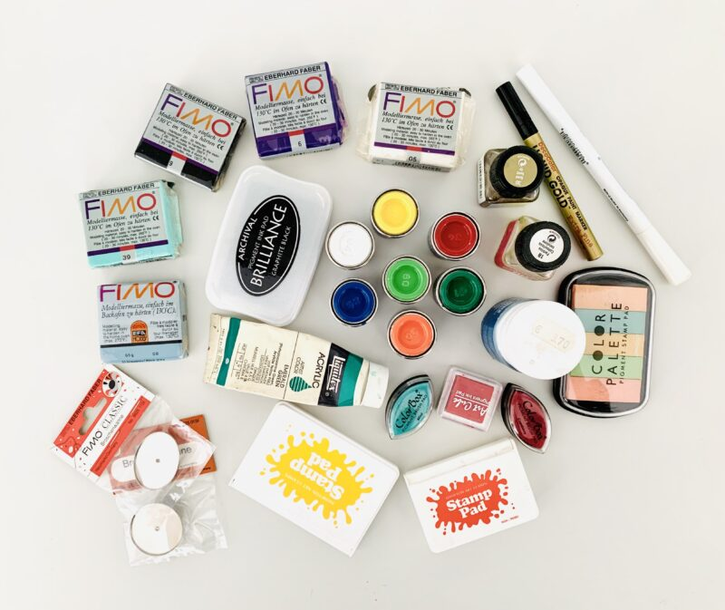 Photo of colourful craft supplies that were sorted out, including inkpads, fimo modelling clay, pens, and paints, all on a white desk.