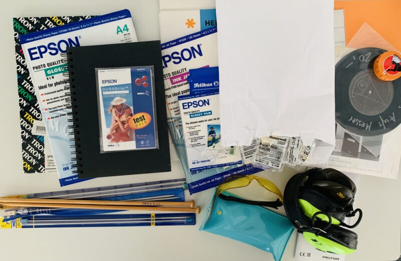 Photo of a bunch of hobby items that were decluttered during a 30 day minimalist game. the hobby supplies include packets of photo inkjet paper, notebooks, knitting needles of different sizes, a 7 inch single, and ear protection usually worn at shooting ranges.