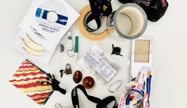 Photo of around 25 pieces of random items typically found in a junk drawer such as masking tape, keychains and lanyards, old CD-Roms, a luggage lock and key, and a hook.