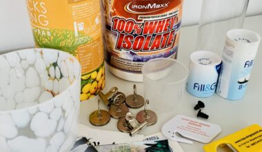 Photo of items from a kitchen clearout decluttering session, including magnets, protein powder, water filters, takeaway menus, and a bottle opener. All the objects are set on a white table in front of a white wall.