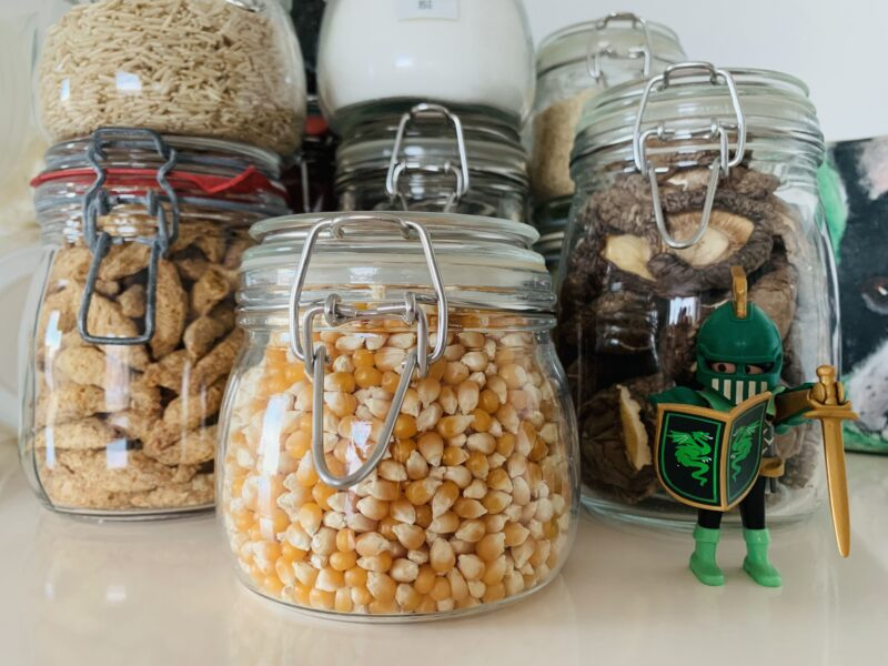 Photo of clean, tidy, glass mason jars containing dried staples such as popcorn, soy puffs, rice, dried mushrooms, MSG and more.
