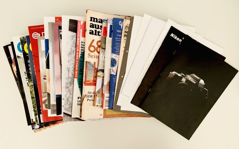 Photo of a stack of old magazines and product brochures laid out on a white table in a fan shape.