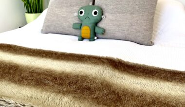 Photo of a tidily made up bed with a white bedspread, greige coloured decorative pillows, a fake fur bed throw, and a rather sad looking sort of stuffed animal. The walls are white and to the left of the bed is a tall bright green plant.