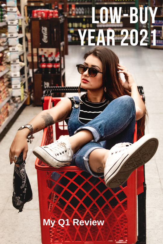 """Girl in denim overalls wearing sunglasses, casually sitting in an empty supermarket shopping cart. The caption reads """"Low-Buy Year 2021. My Q1 Review"""""""