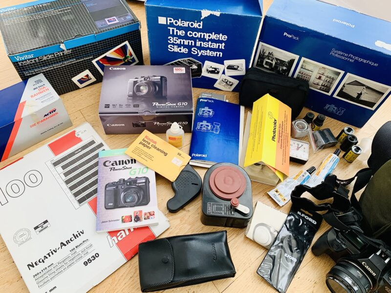 Image shows a huge lot of photographic equipment, cameras, and darkroom supplie decluttered on day 29 of a 30-day challenge. Items include a Polaroid ProPack camera, a Canon G10 digial camera, a Canon EOS 650 camera with EZlight 420, photograph dyes, books, a bulk film loader, instruction manuals and more.