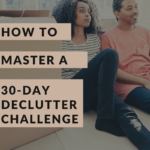 Photo of a young couple sitting on the floor next to a pile of packed up boxes. The woman looks a bit tired, yet pleased, and her man is smiling with satisfaction. Caption reads: How to Master a 30-Day Declutter Challenge. Best tips.