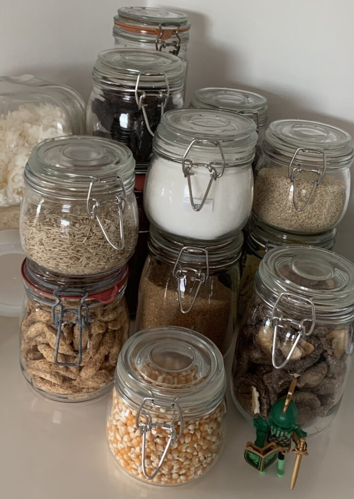 Photograph of glass jars filled with dried foodstuff like brown rice, popcorn maize, dried mushrooms, brown sugar, coconut flakes and tofu puffs. The jars are used in a small kitchen that has no pantry to maximise storage space.