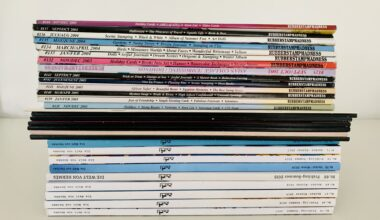 Image shows a tidy stack of decluttered magazines from the side, including issues from Hermès, Rubber Stamp Madness, and Polaroid. The stack has colourful spines and sits atop a white table in front of a white wall.