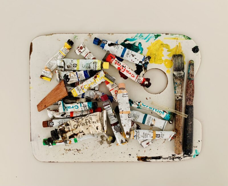 Photo of colourful dried up oil paints and brushes atop a white table.