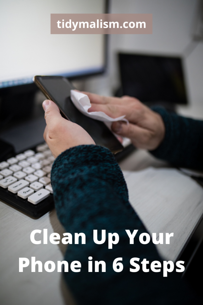 Two hands holding a smartphone at a workstation, and wiping it down with a wet disinfectant wipe. Caption reads Clean Up Your Phone in 6 Steps and is about digital decluttering of smart devices and mobile phones.