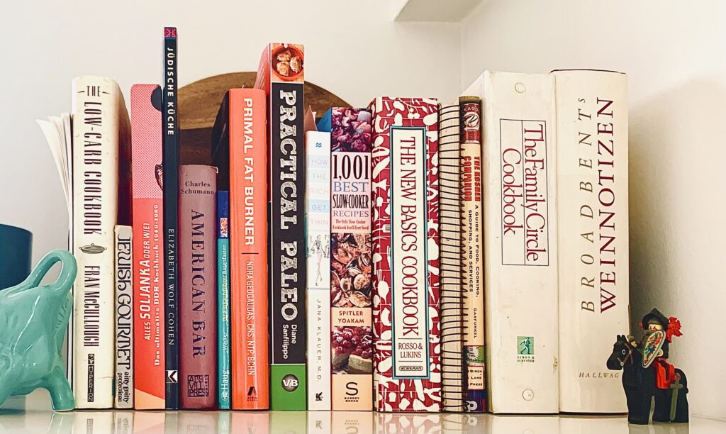 Cookbook collection on a kitchen shelf.