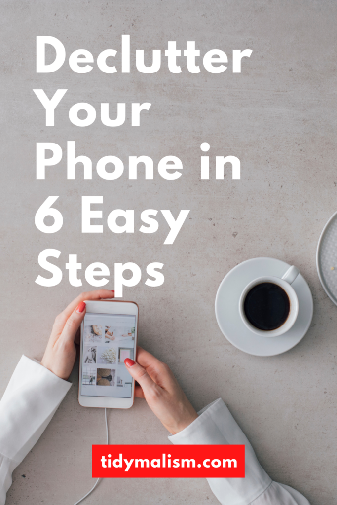 Image of two lady's hands from above, holding a white smartphone. To the right is a coffee in a white porcelain cup. The smartphone, lady's sleeves and tabletop are all white. Caption reads Declutter Your Phone in 6 Easy Steps, tidymalism.com.