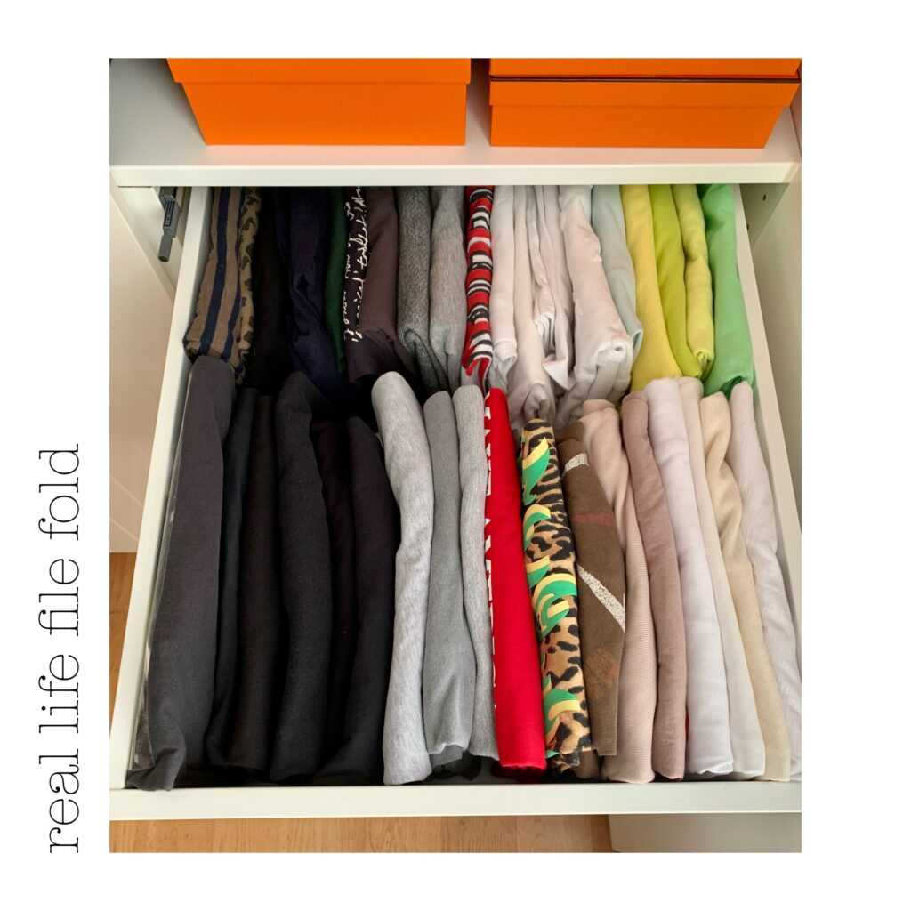 File folding in small drawers. This is drawer of t-shirts that have been file folded. We can see all the colours and have more space. The front horizontal row holds regular tees, and the back row has sleeveless tshirts.