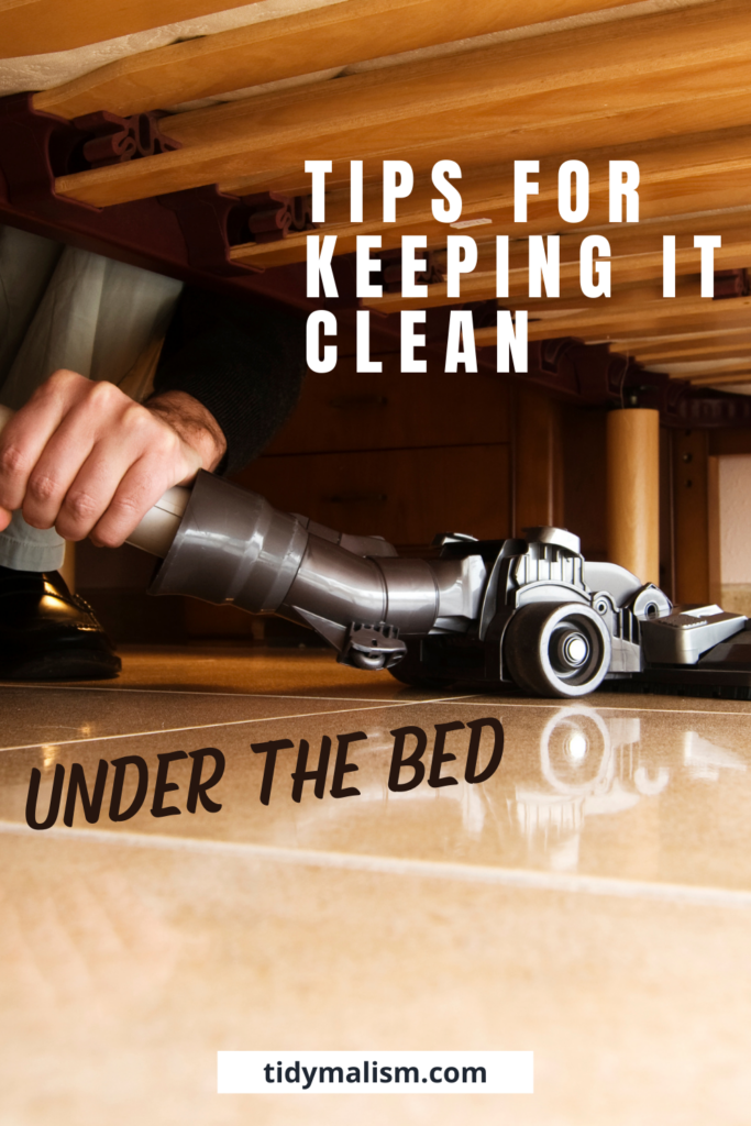 """Image shows a man's hand vacuuming under neath the bed. We can see he is kneeling to get the hoover under the bed. There is no clutter or dust under the bed, and the floor looks very clean. The caption reads """"Tips for keeping it clean under the bed"""" and takes us to an article about how under bed storage is bad because it causes dust, and how to keep dust at bay in the bedroom and under the bed."""