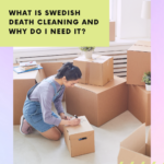 Young lady in denim overall shorts and grey long-sleeved t-shirt kneeling over packing and moving boxes. She is labelling one box with a black marker. Caption reads: What is Swedish death cleaning and how can it help me get organized?