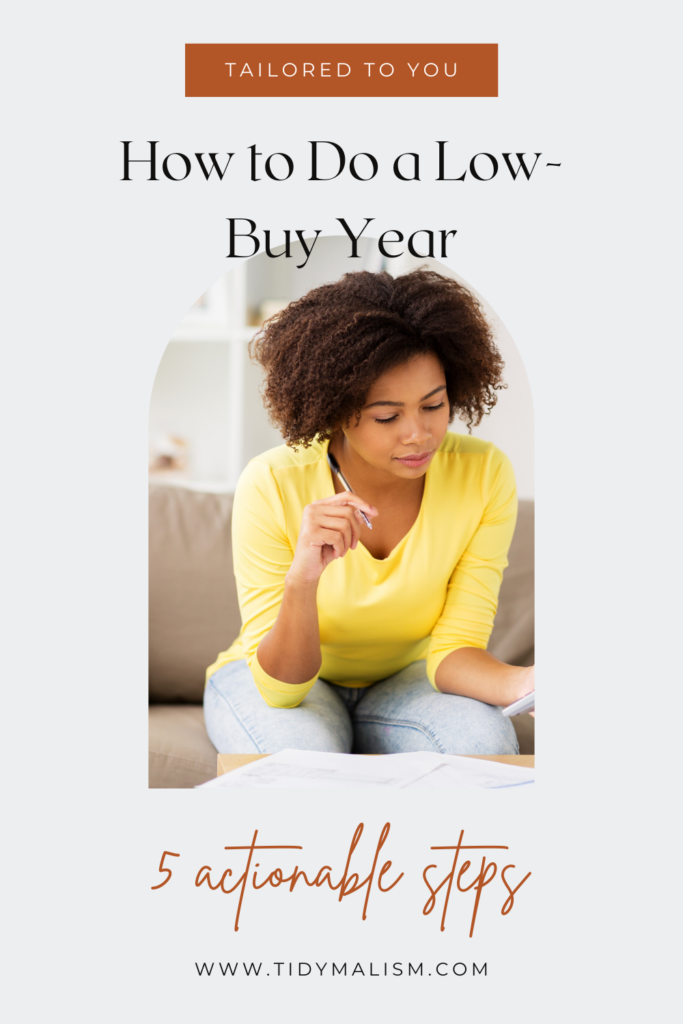 Young lady in a yellow shirt, sitting on the couch, holding a pen in her hand and looking over her accounts. Caption reads: Tailored to you: how to do a low buy year. 5 actionable steps. www.tidymalism.com