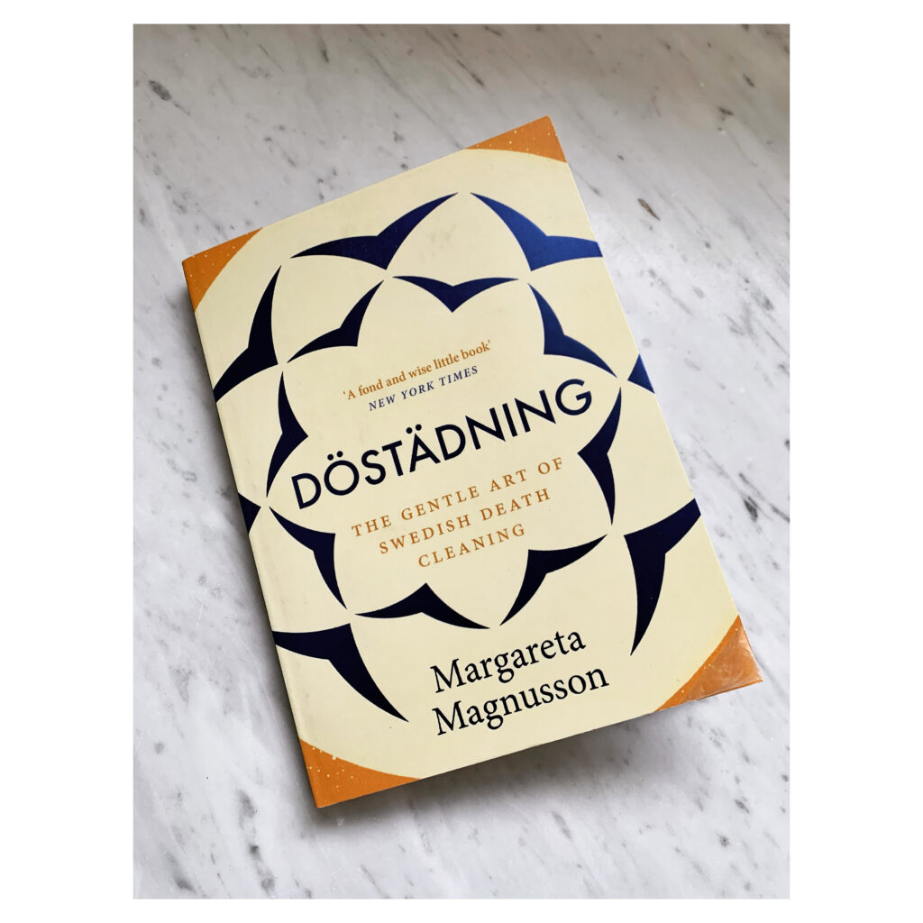 """paperback copy of Margareta Magnusson's book """"Döstädning. The Gentle Art of Swedish Death Cleaning"""" lying on a white carrara marble countertop"""