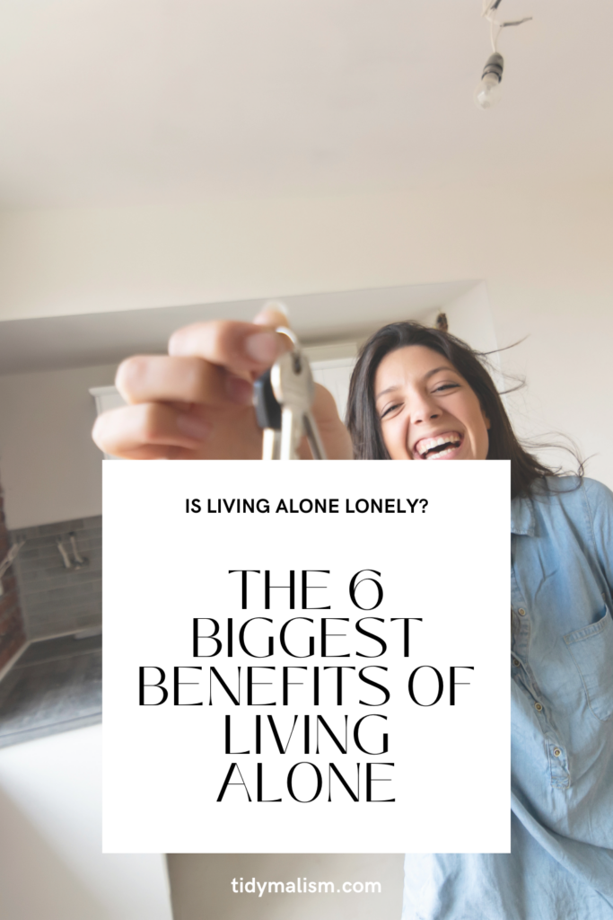 Young lady happily holding the keys to her new home and smiling. Caption reads: Is living alone lonely? The 6 biggest benefits of living alone. tidymalism.com