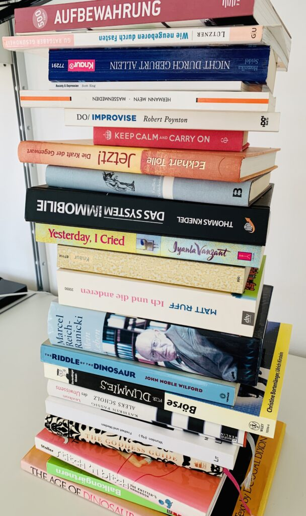Huge stack of English and German language books piled high on a white desktop. Article is about organising during heat waves and includes book decluttering as an ideal project to take on during hot weather.