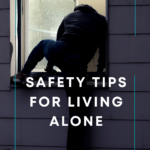 Robber clad in black climbing through a well-lit window of a house in the evening to break in. Caption reads safety tips for living alone, tidymalism.com.