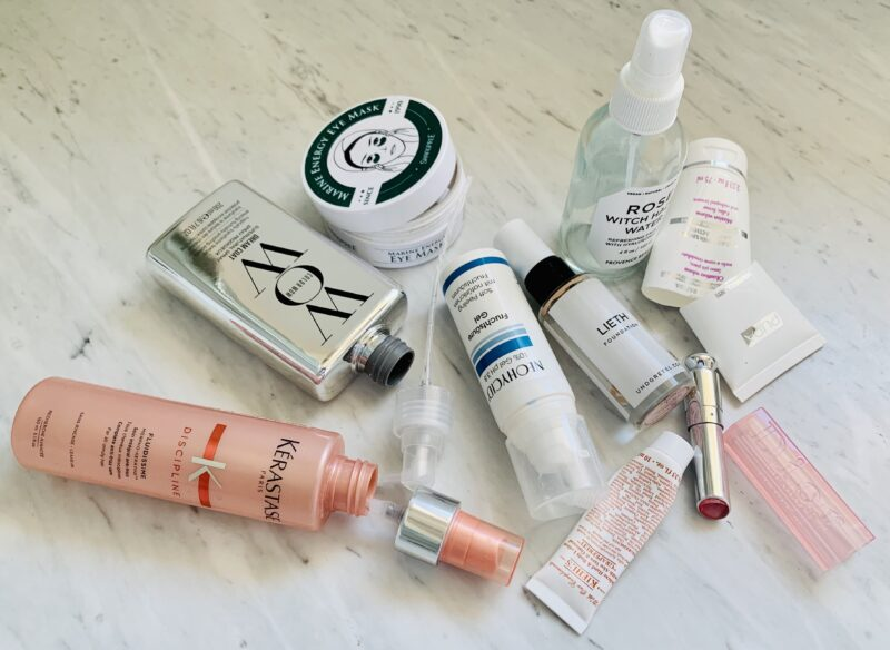 Close up photograph of an assortment of empty beauty products. Tubes, plastic vials, glass bottles all randomly lying about on a marble countertop. Some of the bottles are open and lying on their side. Some of the tubes are cut in half and we can see that the remainig product was really used up.