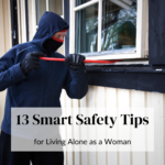 A masked robber trying to break an entry on the ground floor of a house. He is using a crowbar to leverage out the window and break in. Caption reads: 13 smart safety tips for living alone as a woman. Read more at tidymalism.com.