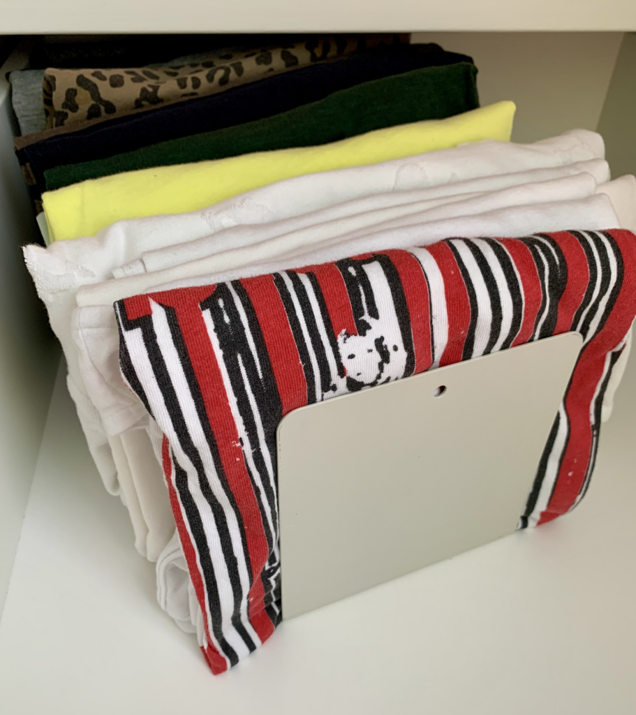 Photo of file-folded t-shirts in a closet drawer, which are kept propped up in place by using a simple metal bookend as part of Tidymalism's home organisation strategies.