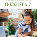 Young lady in jeans and a white-navy striped t-shirt hunched over her desk working on a checklist in her notebook. Caption reads: Free PDF printable decluttering checklist from A to Z. Best tips for decluttering from tidymalism.com.