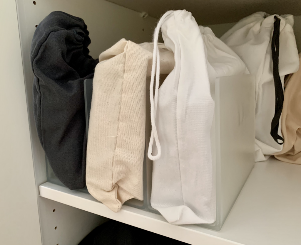 Photo of a vertical file holder from the office supply department repurposed to organise clutches and slim handbags in the closet as one of the article's featured home organisation strategies.