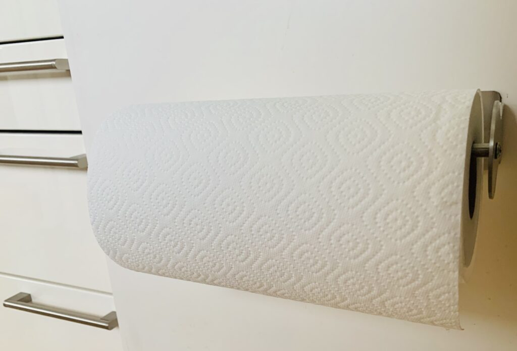 Photo of a stainless steel paper towel holder with a roll of white paper towels on it, hidden inside of a lower cabinet in a small kitchen to maximise space.