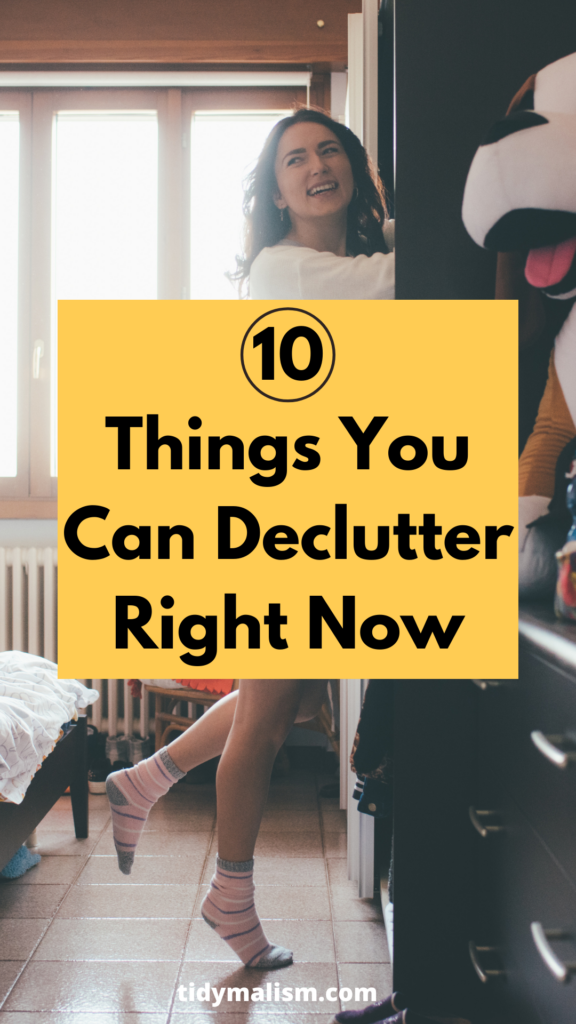 Young lady wearing just socks and a top, standing on her tip toes to reach into her open closet system. She's looking back to her right and smiling widely. She seems to be decluttering and tidying things up. Caption reads: 10 things you can declutter right now.