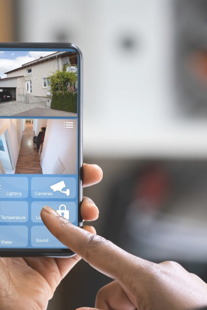 Photograph of two hands holding a mobile phone in video mode, doing a walk-through of a home to make a video tour to complement the home inventory spreadsheet used to track household items.