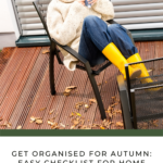 Brunette lady with hair pulled back in a ponytail, sitting on her deck in an oversized cable-knit jumper, jeans, and yellow wellies. There are fallen leaves around her chair and it's clearly autumn. She's drinking a cup of tea and smiling.