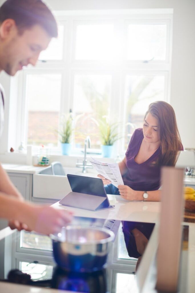 A couple in a bright and sunny kitchen. He is standing at the stove stirring something, and she is inputting receipt amounts into a home inventory spreadsheet on her tablet.