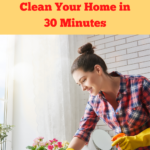 Woman in her late 20s wearing a red and blue flannel shirt and yellow rubber gloves. She's quickly wiping down the top of a white shelving unit at hip height in front of a floodlit window. There are plants on and around the shelf. She's using glass cleaner and a rag to clean. Caption reads 8 easy steps to speed clean your home in 30 minutes.