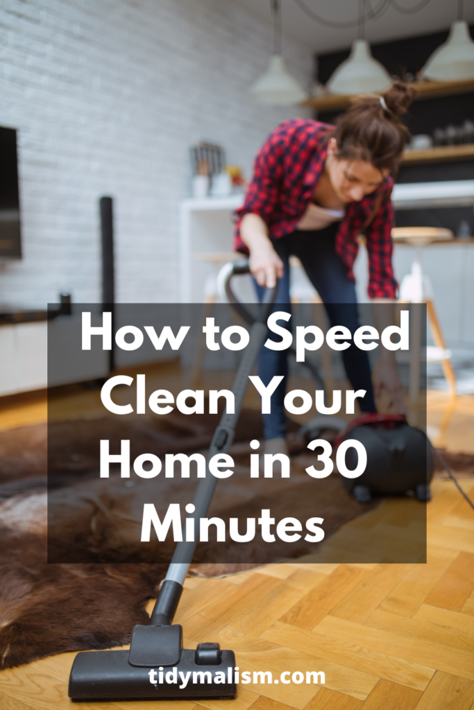 Young lady in red flannel shirt quickly vacuuming her living room hardwood floors and area carpet. She is hunched over her hoover to pull its cable out. Caption reads how to speed clean your home in 30 minutes.